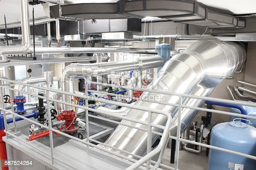 View on the interior of a building boiler room, with cooling and heating system of pipelines