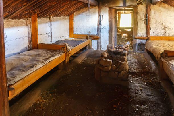 innenraum einer hütte mit betten und einem kamin in einem restaurierten haus - bauernhaus bett stock-fotos und bilder