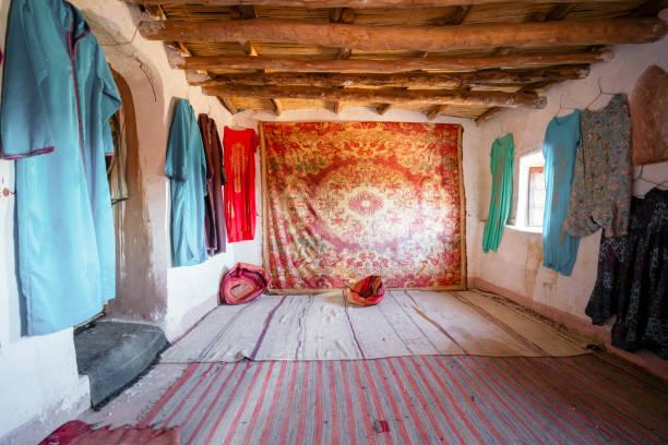 Das Innere eines historischen Zimmers mit Berberteppich und Kleidung in Ait Ben Haddou, Marokko – Foto