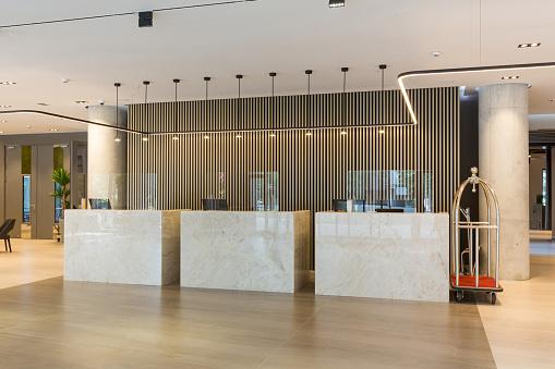 Interior of a hotel lobby with reception desks with transparent coronavirus plexiglass lexan clear sneeze guards