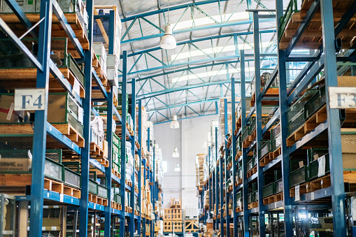 Interior of a large distribution warehouse. Rows of big racks and shelves in factory storage room.