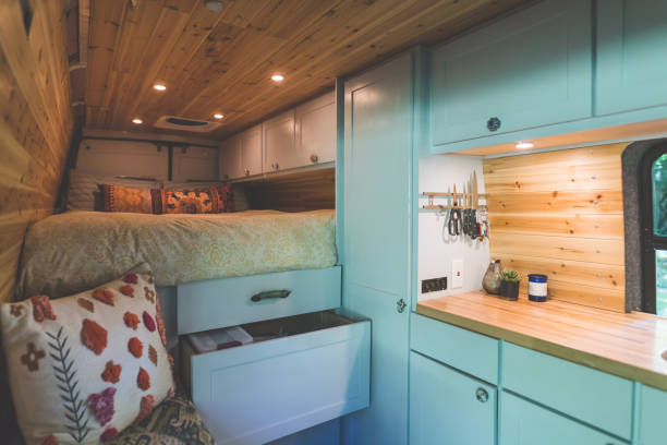 Interior of a live-in van Interior of a van that a young couple live in. The shot is focused on the kitchen counter, pull-out drawers, and bed. Ther is wood paneling on the sides and roof. rv interior stock pictures, royalty-free photos & images