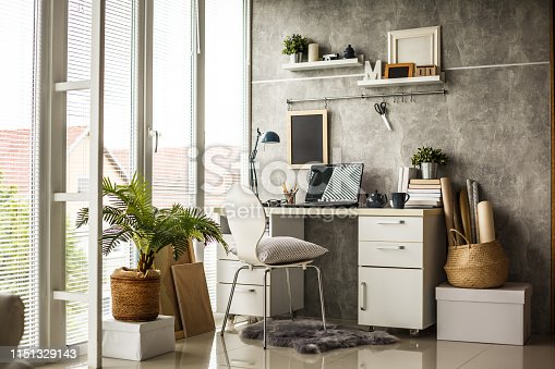 Interior of a modern home office next to a big window. Light wood desk with organized set up of books, office supplies and laptop with some room decor around it.