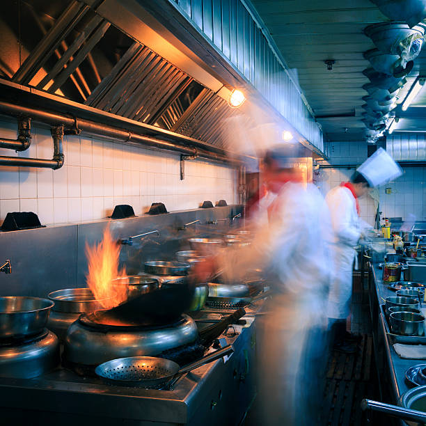interior of a restaurant kitchen with busy chefs - busy restaurant kitchen stock pictures, royalty-free photos & images