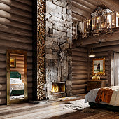 Interior decoration of log cabin bedroom. Big mirror by the fireplace with artifacts in winter cottage bedroom.
