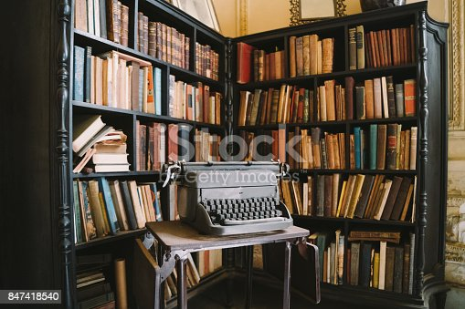 istock Interior of abandoned ornate Colonial Villa with books and typewriter 847418540