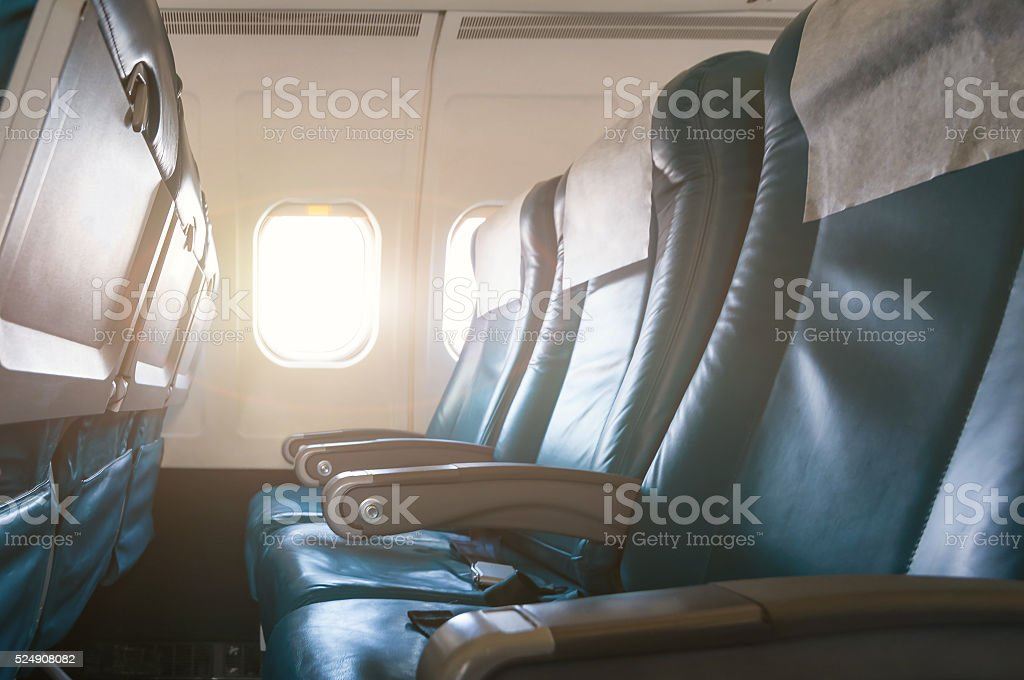 Interior of airplane with empty seats and sunlight at the stock photo