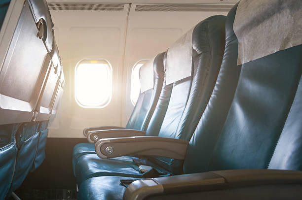 Interior of airplane with empty seats and sunlight at the Interior of airplane with empty seats and sunlight at the window. Travel concept. airplane seat stock pictures, royalty-free photos & images