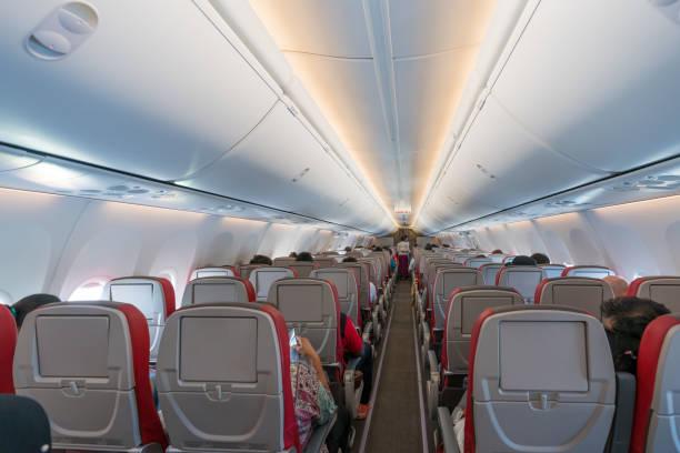 Innenraum des Flugzeugs mit Passagieren auf Sitze und Stewardess in Uniform zu Fuß den Gang. – Foto