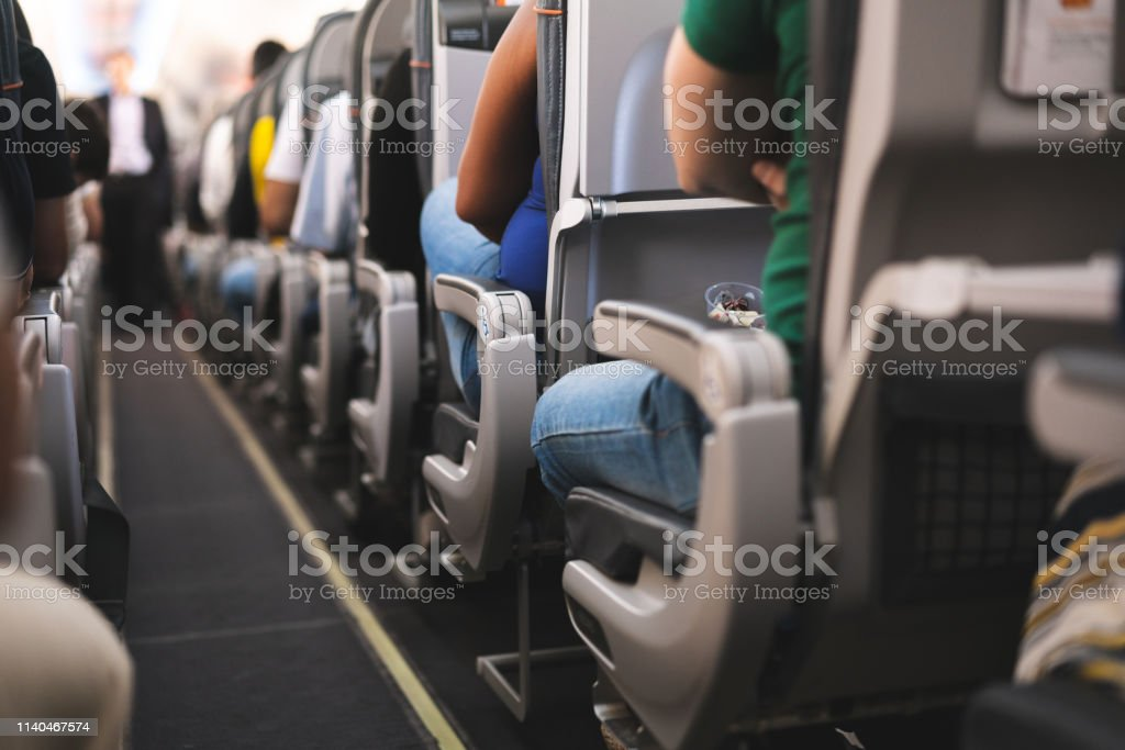 Interior of airplane with passengers on seats Air Vehicle, Airplane, Commercial Airplane, Luggage, People Adult Stock Photo