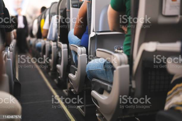 Interior Of Airplane With Passengers On Seats Stock Photo - Download Image Now