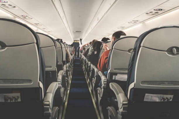 Interior of airplane with passengers on seats waiting to taik off. stock photo