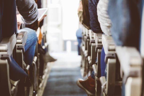 Interior of airplane with people travelling Rear view of commercial airliner cabin with passengers. Interior of airplane with people sitting on seats. airplane seat stock pictures, royalty-free photos & images