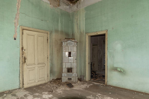 Interior of an abandoned mansion. Empty room deserted and derelict. The interior of an abandoned castle. Damaged and demolished fireplace stock photo