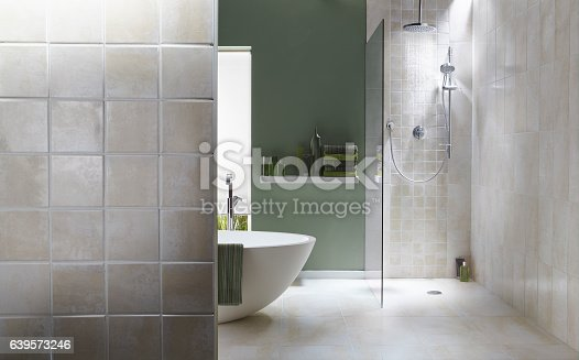 The interior of a simple, modern bathroom in a cool, green tone. There is a bath, shower, a bath towel . There are light grey tiles in the shower with running water
