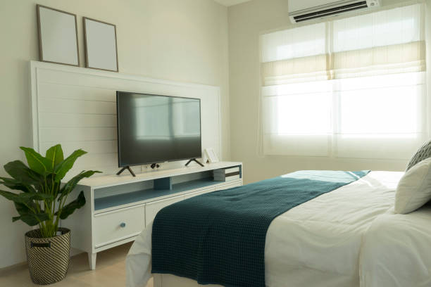 Interior of bedroom with big TV on the cabinet stock photo