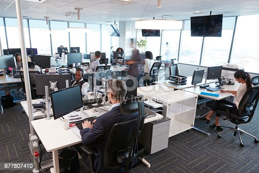 istock Interior Of Busy Modern Open Plan Office With Staff 677807410
