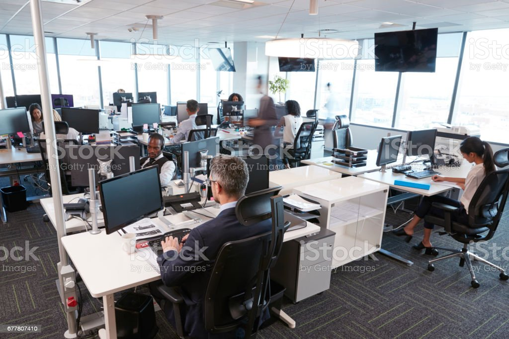 Interior Of Busy Modern Open Plan Office With Staff - foto de stock