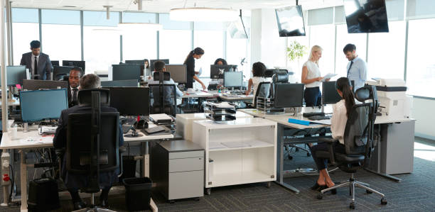 interior of busy modern open plan office with staff - busy stock photos and pictures