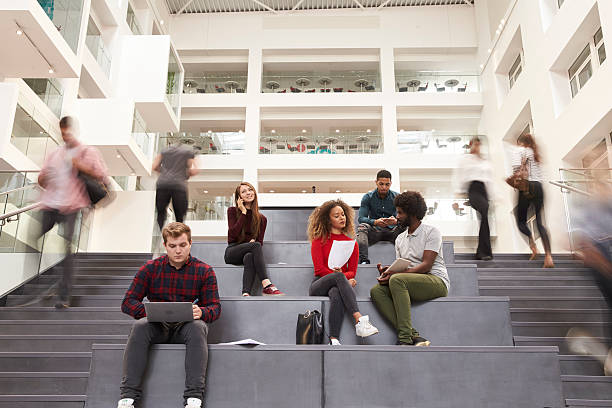 interior of busy university campus building with students - adult student stock photos and pictures