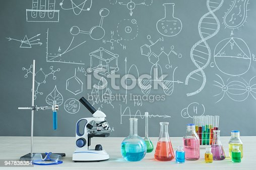 Interior of modern chemistry classroom: desk with microscope and laboratory glassware, blackboard with inscriptions, no people