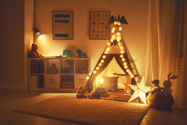 innere des kinderspielzimmer mit zelt, lampen und spielzeug im dunkeln - schlafzimmer beleuchtung stock-fotos und bilder