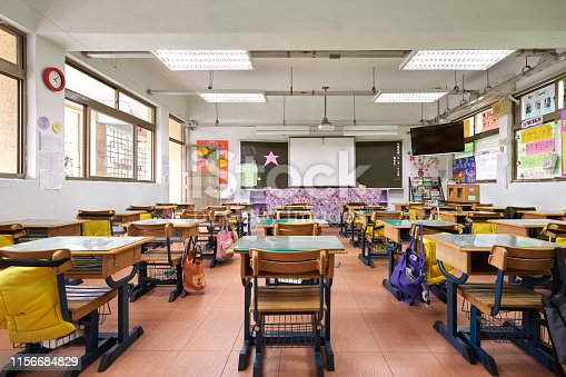 Interior of classroom in elementary school. Row of empty desks are in illuminated room.