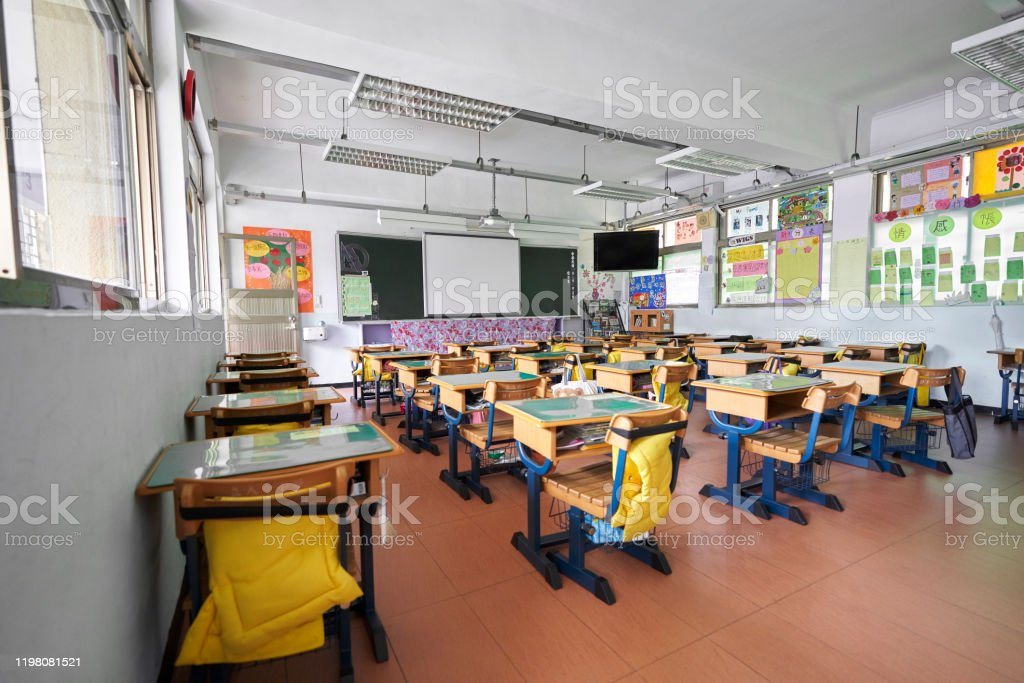 Interior of classroom in elementary school Interior of classroom in elementary school. Row of empty desks are in room. Absence Stock Photo