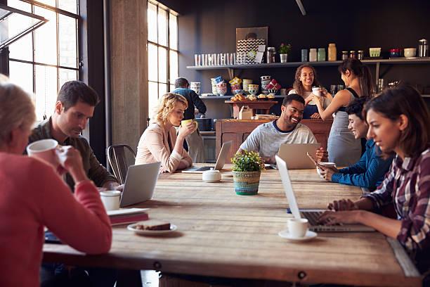 innenausstattung des kaffee shop mit kunden unter verwendung digitaler geräte - coffee shop stock-fotos und bilder