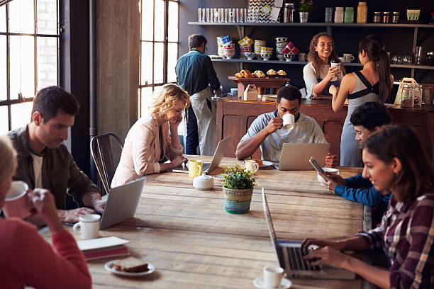 Interior Of Coffee Shop With Customers Using Digital Devices Interior Of Coffee Shop With Customers Using Digital Devices coffee shop stock pictures, royalty-free photos & images
