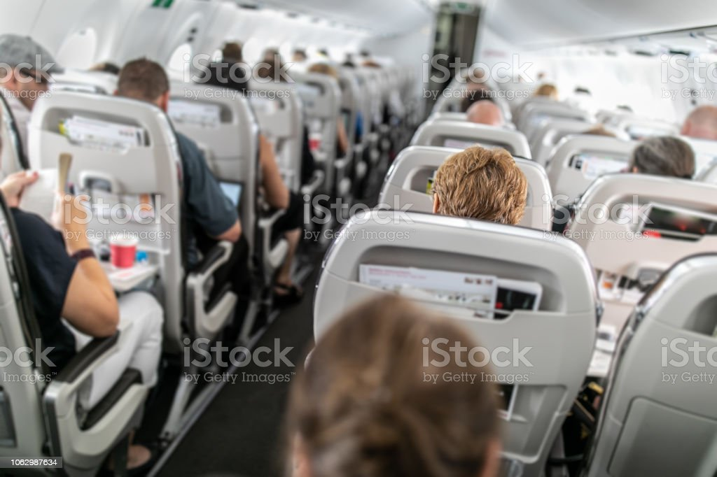 Interior of commercial airplane with passengers in their seats Interior of commercial airplane with passengers in their seats during flight. Adult Stock Photo