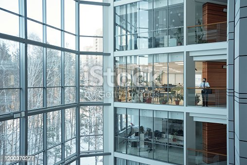 Interior of contemporary multi-floor business center with large windows and many offices in front of them