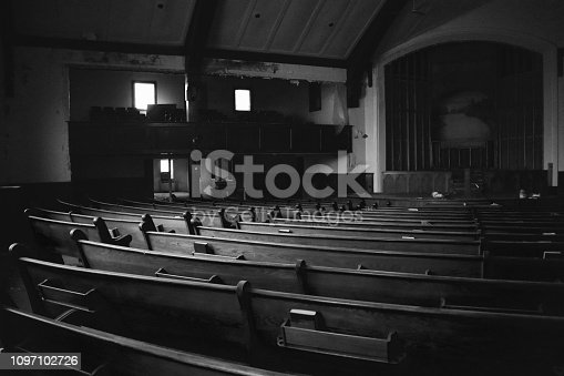 Church with no people with lighting from sun during day showing arched stage and benches.
