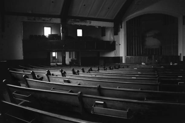 Interior of empty church in monochrome with light from windows illuminating wooden pews, stage, and altar. Church with no people with lighting from sun during day showing arched stage and benches. pew stock pictures, royalty-free photos & images