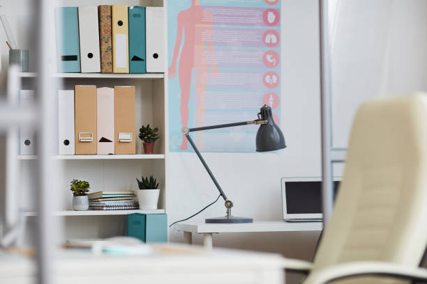 Interior of empty doctors office with body description banner on wall, lamp and laptop on table, shelves full of folders stock photo