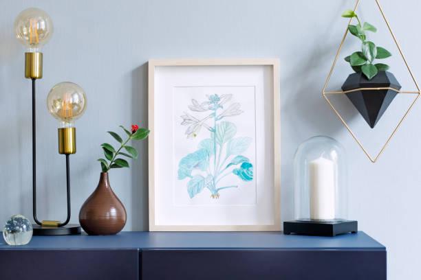 intérieur d'affiche floral mock up avec armature en bois vertical, lampe de table, accessoires, bougie et pendaison plantes en pot géométrique sur le fond du mur gris. concept avec étagère bleu marine. - camera sculpture photos et images de collection