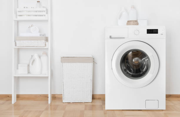 Interior of home laundry room with washing machine near wall stock photo