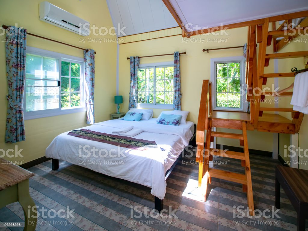 Interior of hotel resort with bed and wooden ladder stock photo