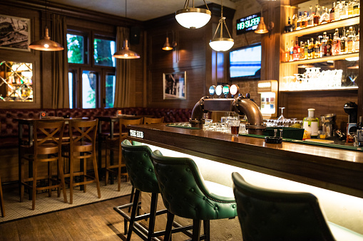 Interior of wooden retro pub with chairs, tables and other furniture, without people
