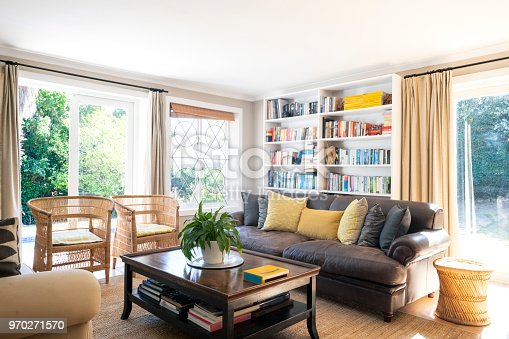 Sofa and chairs in living room. Interior of simple home. Furniture is arranged in sitting area.
