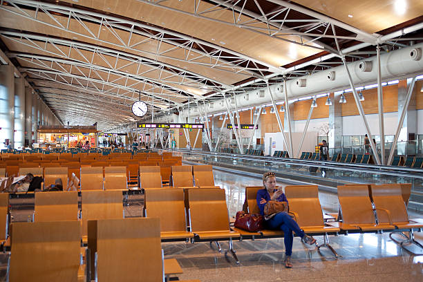 Interior of Madrid's airport with passenger waiting to depart Madrid, Spain - June 2, 2014: Interior of Madrid's airport with passenger waiting to depart. Departure aria with glossy floor reflecting the lights, clock and shops in distant depart stock pictures, royalty-free photos & images