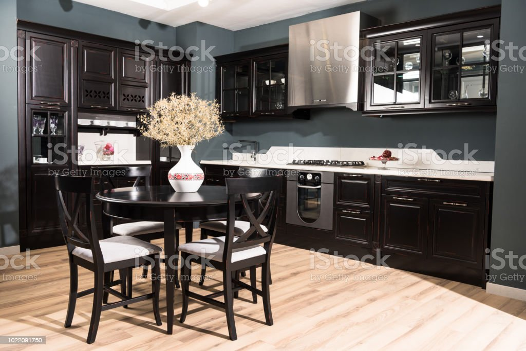 Interior Of Modern Kitchen And Dining Room With Black Wooden Furniture And Vase Of Dried Flowers On Table Stock Photo Download Image Now Istock