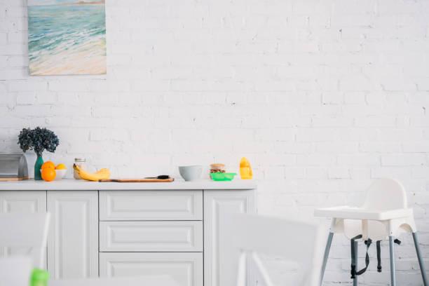 innere des modernen leichten küche mit früchten auf tisch und stuhl - kinderstuhl und tisch stock-fotos und bilder