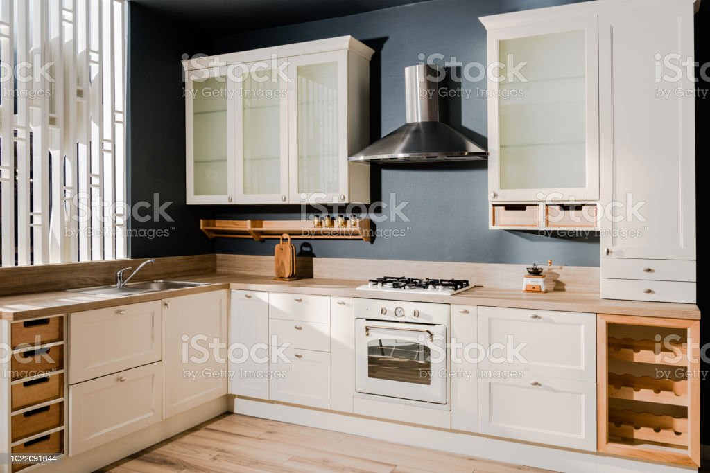Interior Of Modern Light Kitchen With White Wooden Kitchen Counters Shelves  And Stove Stock Photo - Download Image Now