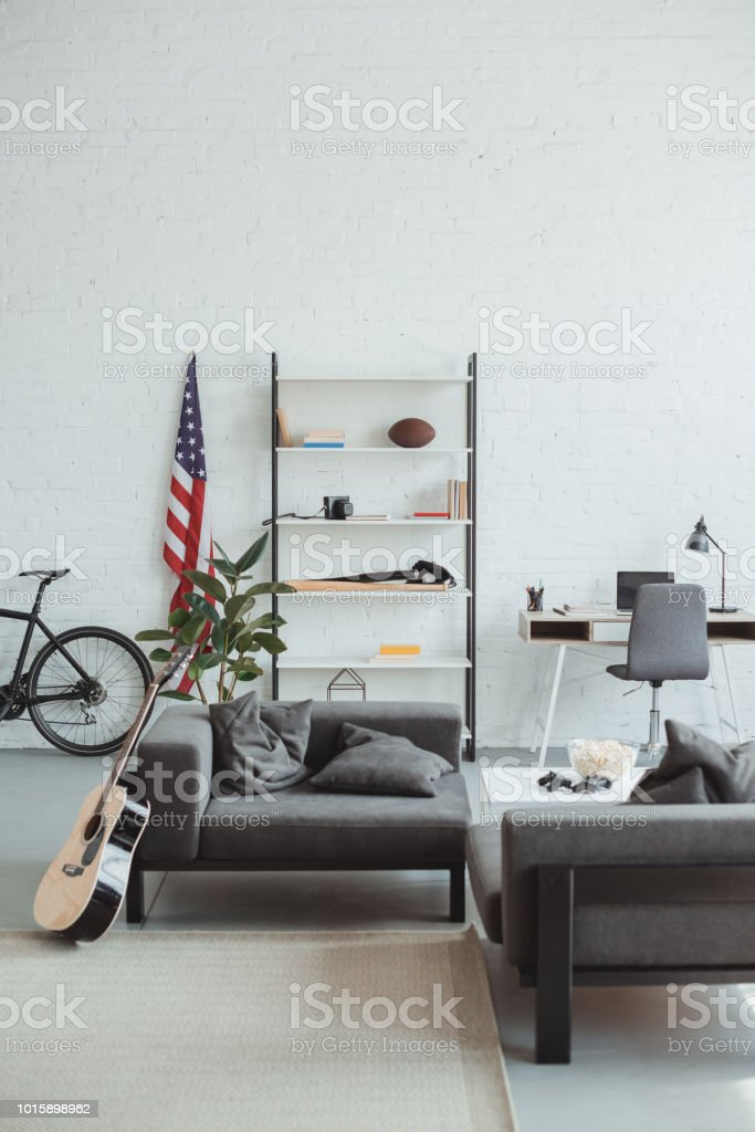 interior of modern living room with bicycle, guitar, american flag, laptop, shelves and armchairs stock photo