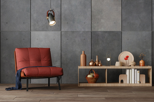 Interior Of Modern Living Room With Red Armchair, Decorative Objects On The Cabinet, Gray Colored Wall And Parquet Floor