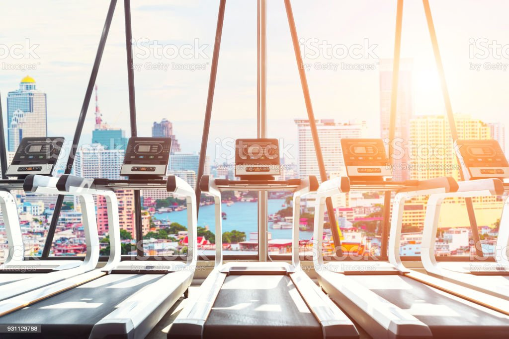 Interior of modern treadmills in gym at sunrise with view of city...
