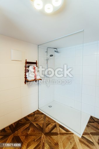 istock Interior of modern white bathroom with wood design shower 1139714939