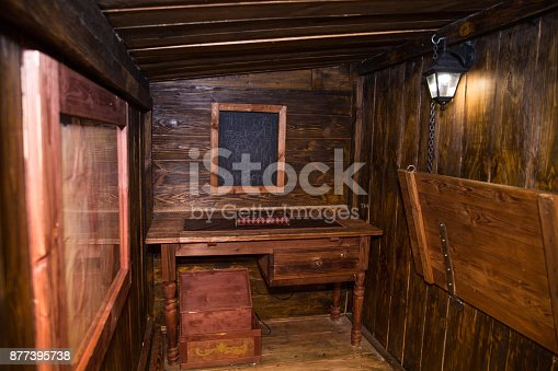 Interior of old ship cabin with wooden panels and cords. Lantern, Chest, Table Board