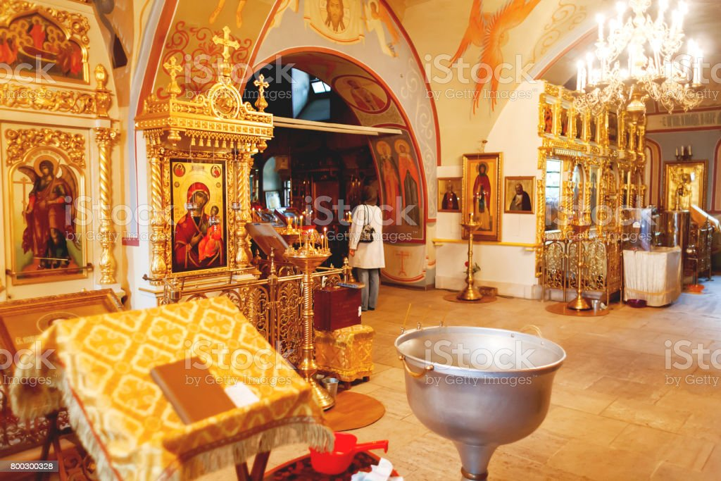 Interior of Orthodox church. Symbolic Orthodox gold cross with the crucifixion of Jesus, golden candleholders and other details. stock photo